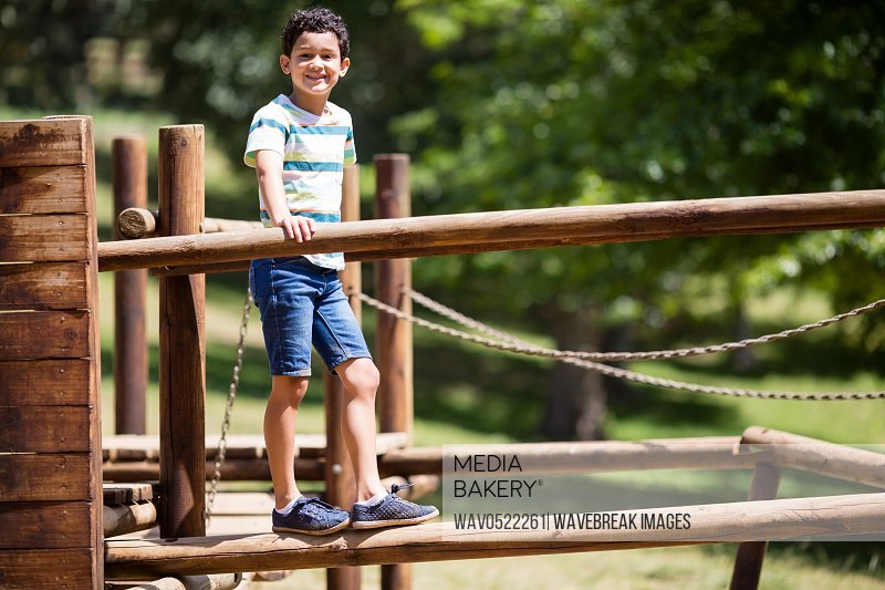 Boy standing on a playground ride in park