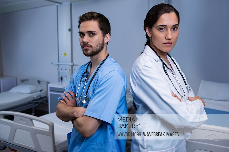 Portrait of male nurse and doctor standing with arms crossed in ward