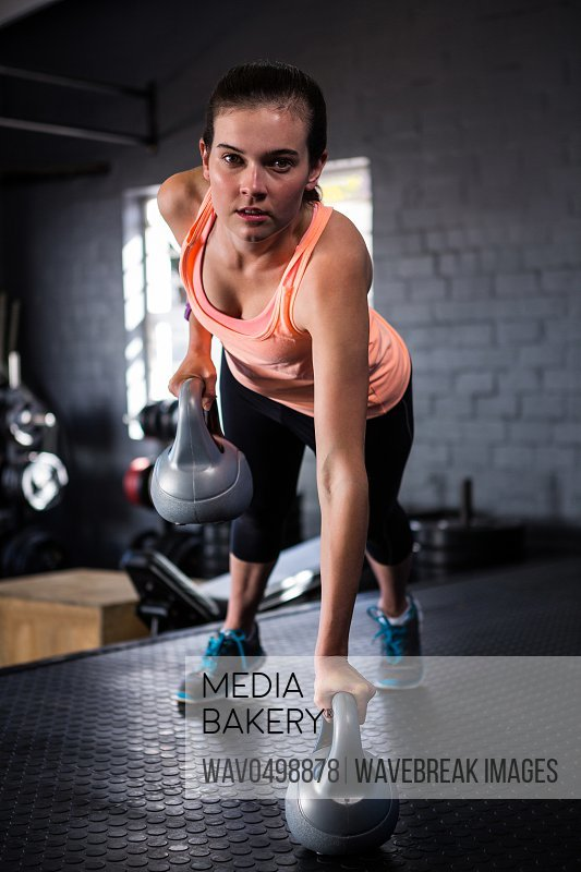 Portrait of sporty young woman holding kettlebell while exercising in gym