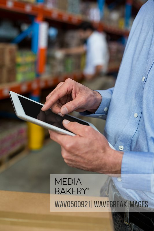 Mid section of warehouse worker using digital tablet in warehouse