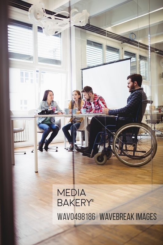 Businessman on wheelchair with photo editors in meeting room at creative office