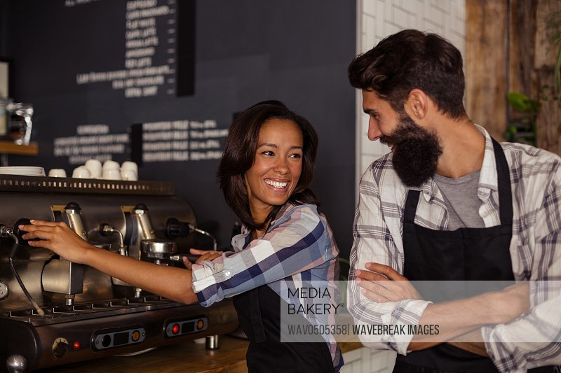 Waiter and waitress interacting while working in kitchen at cafe