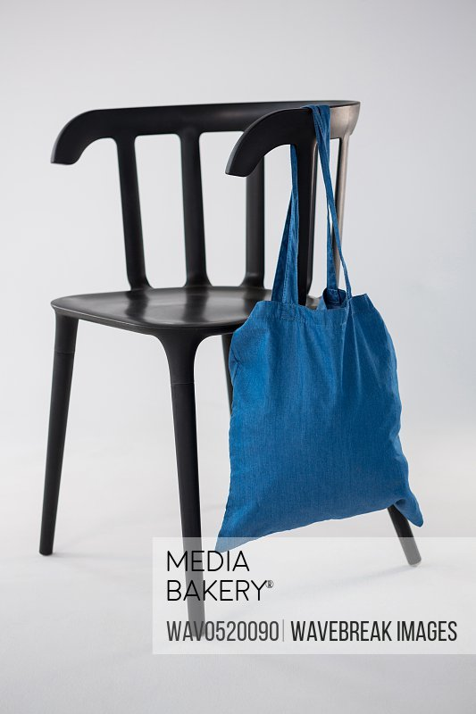 Blue bag hanging on a black chair