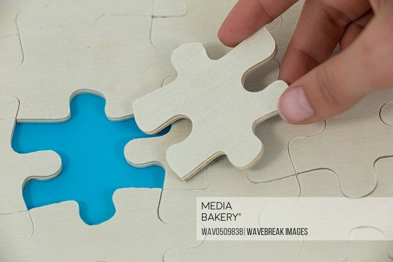 Womans hand placing missing piece in jigsaw puzzle