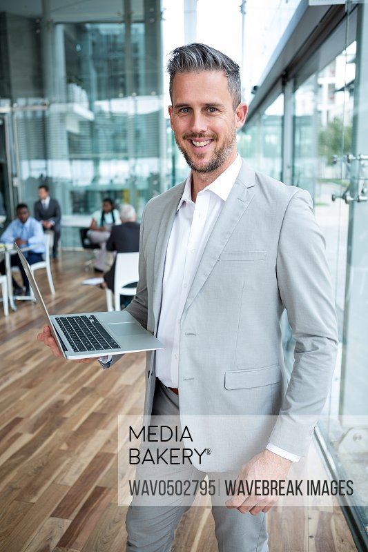 Portrait of smiling businessman holding laptop in the office