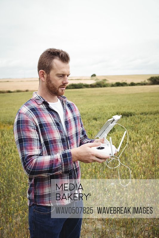 Farmer using agricultural device while examining in field on a sunny day