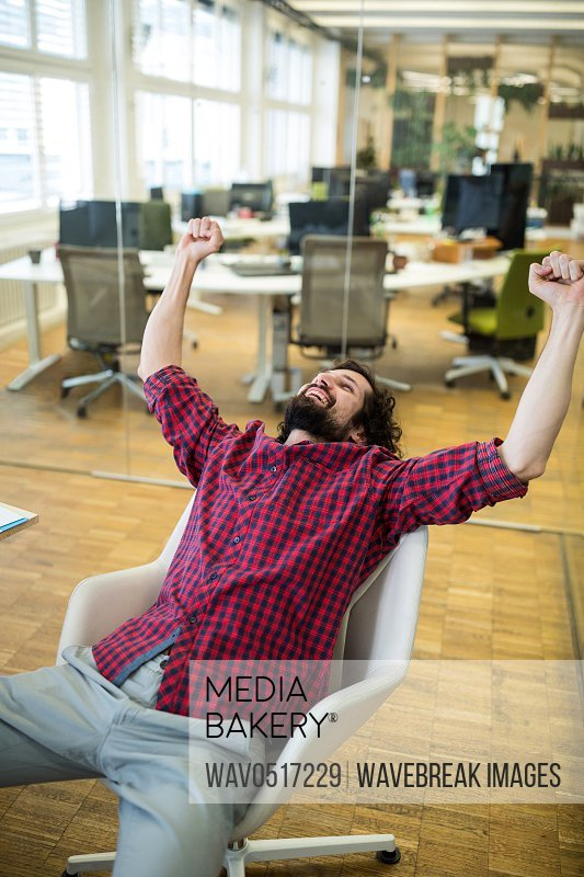 Business executive clenching fist in office