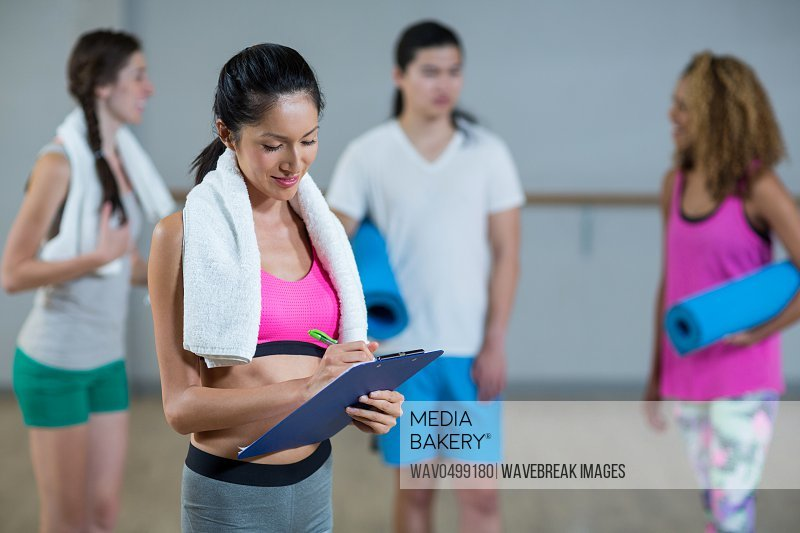 Female trainer writing on clipboard in fitness studio