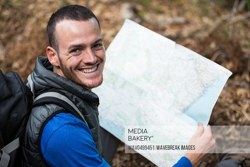 Portrait of smiling male hiker holding a map in forest