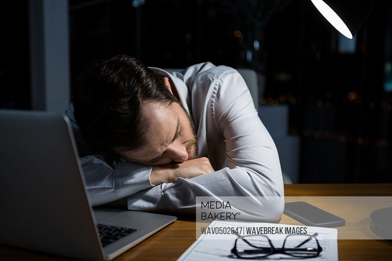 Tired businessman sleeping on the desk in office at night