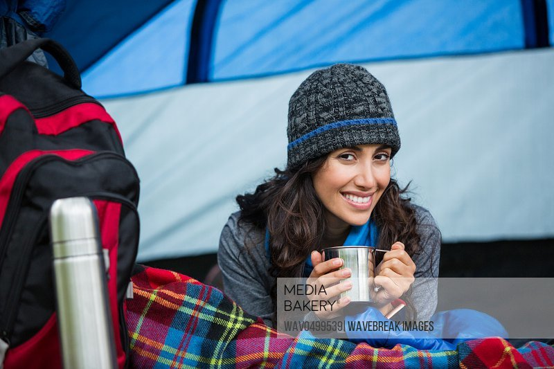 Portrait of smiling hiker having a cup of coffee in tent at forest