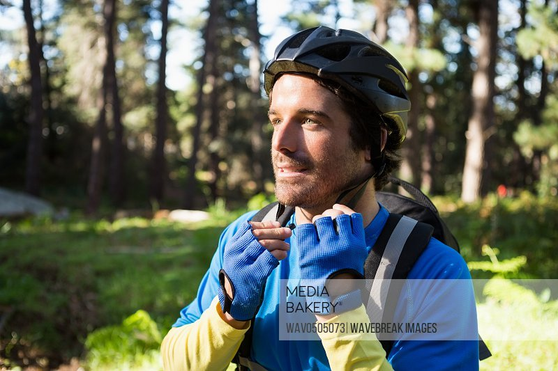 Male mountain biker wearing bicycle helmet in the forest on a sunny day