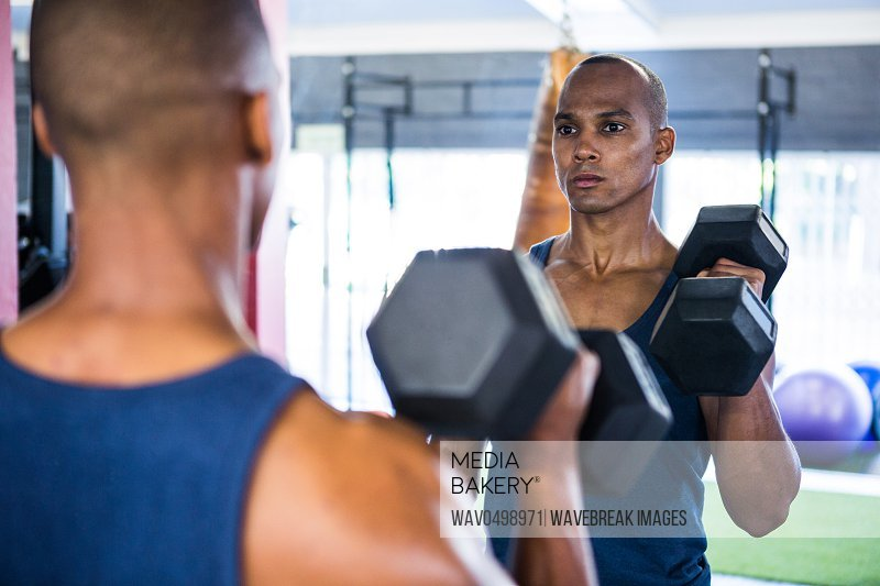 Reflection of male athlete exercising with dumbbell on mirror in gym