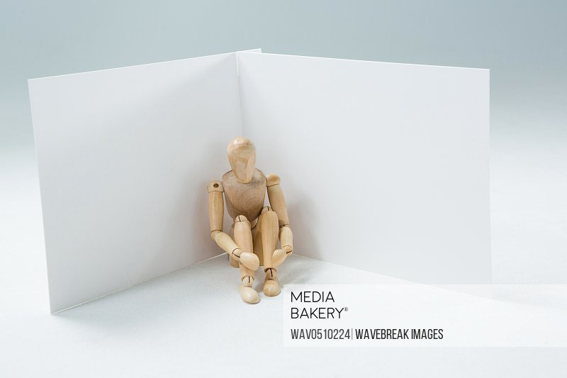 Wooden figurine sitting against wall against white background