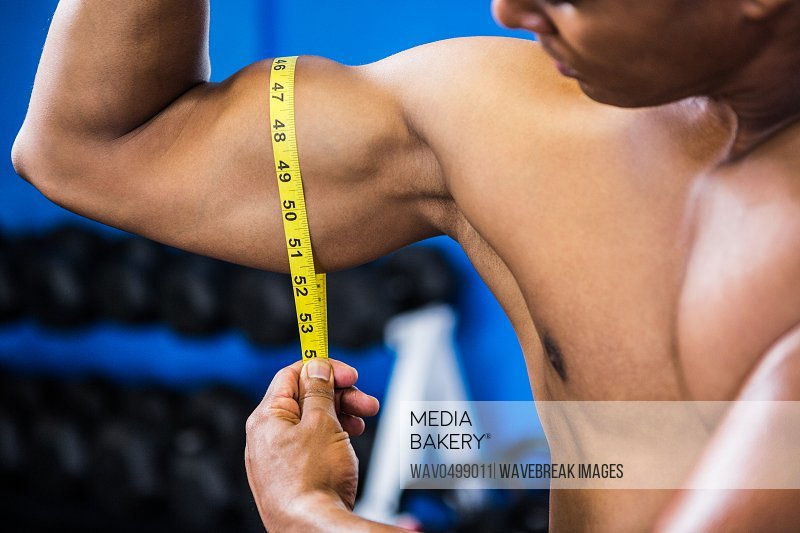Cropped image of muscular man measuring biceps with tape measure in gym