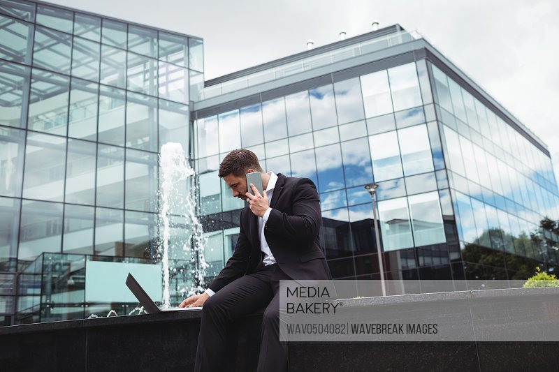 Businessman using laptop while talking on phone in office building