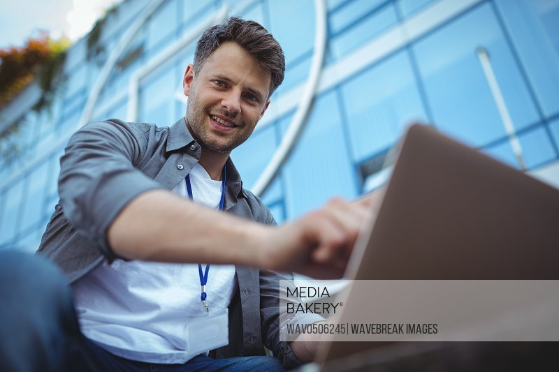 Portrait of business executive using laptop outside office