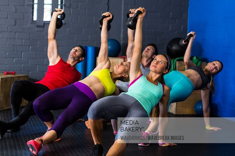 Young athletes exercising with kettlebells in fitness studio