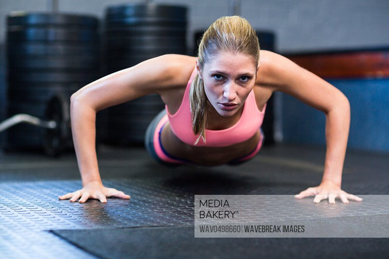 Portrait of determined woman doing push-ups in gym