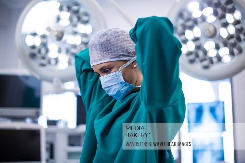 Female surgeon wearing surgical mask in operation theater of hospital