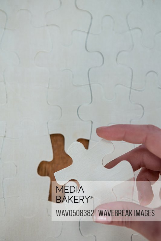 Woman hand placing missing piece in Jigsaw puzzle