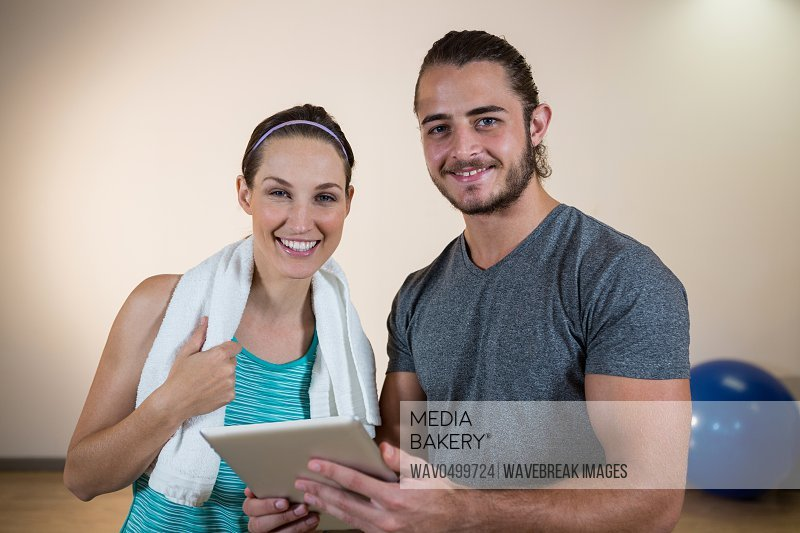 Portrait of fitness trainer and woman with digital tablet in fitness studio