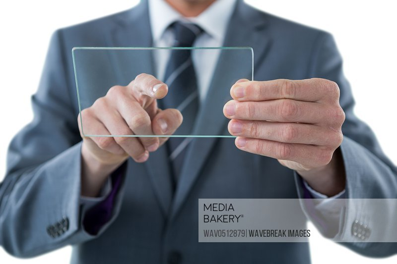Mid section of businessman touching an glass sheet against white background