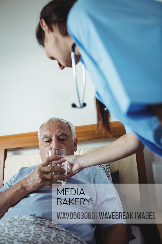 Nurse giving a glass of water to senior man at home