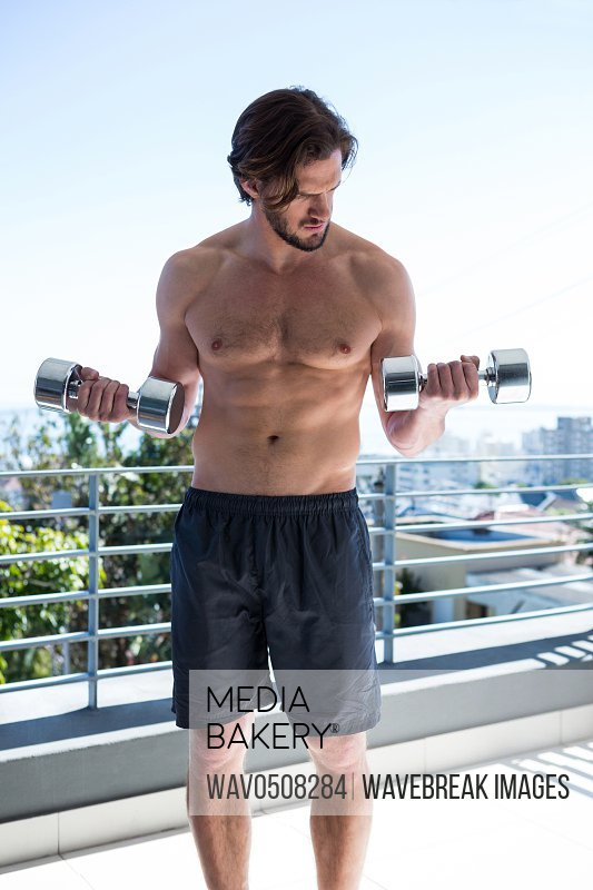 Man exercising with dumbbells in balcony at home