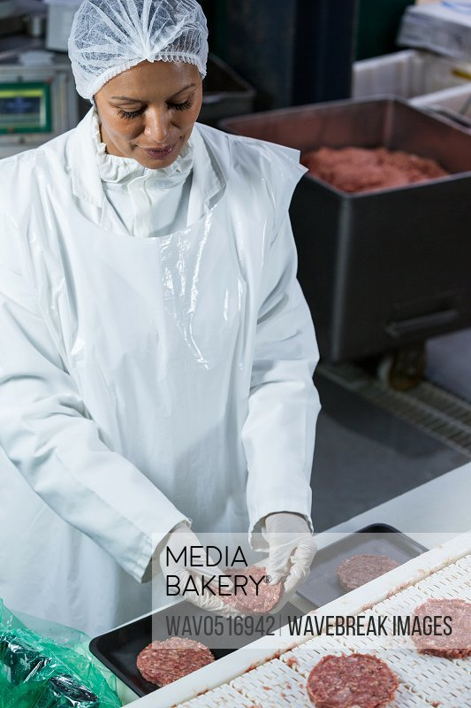 Female butcher arranging hamburger patty on tray