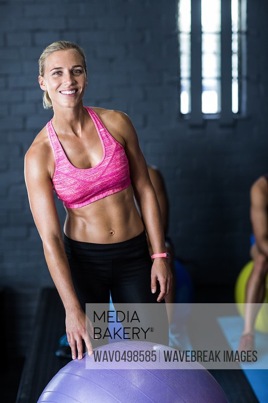 Portrait of smiling female athlete standing by exercise ball in fitness gym