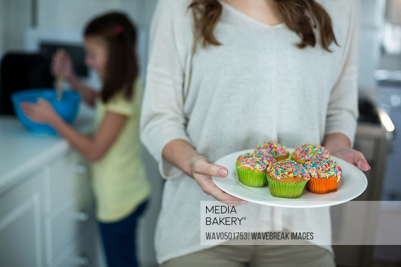 Mid-section of woman holding a plate of cupcakes in kitchen