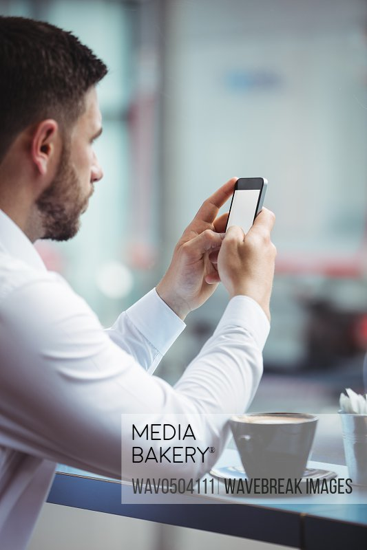 Man using mobile phone while having a cup of coffee in office
