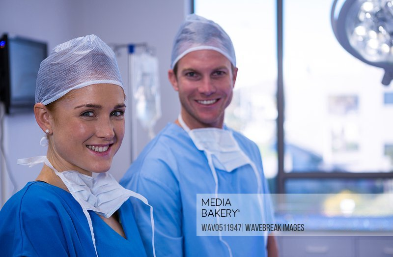 Portrait of male and female nurse smiling in operation theater at hospital