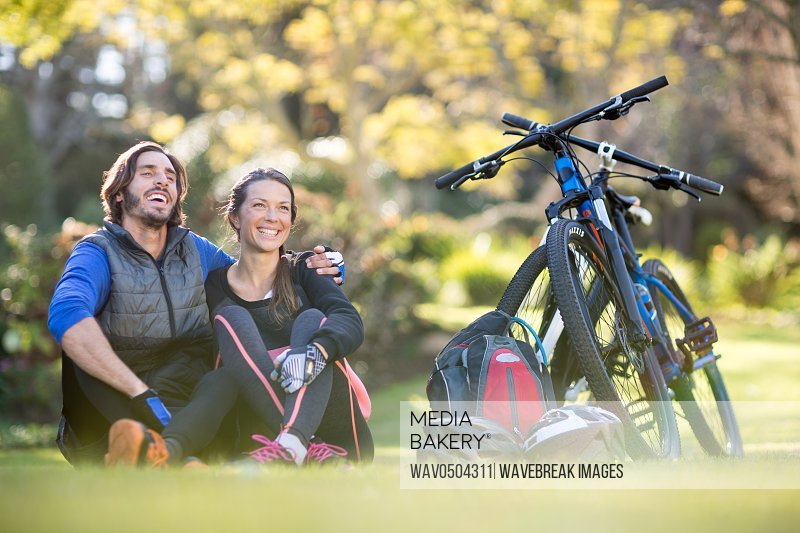 Biker couple relaxing together in countryside park