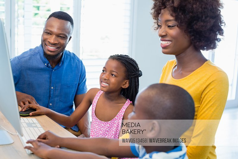 Happy family using computer in living room
