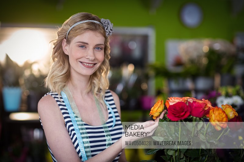 Female florist touching rose flowers in the flower shop
