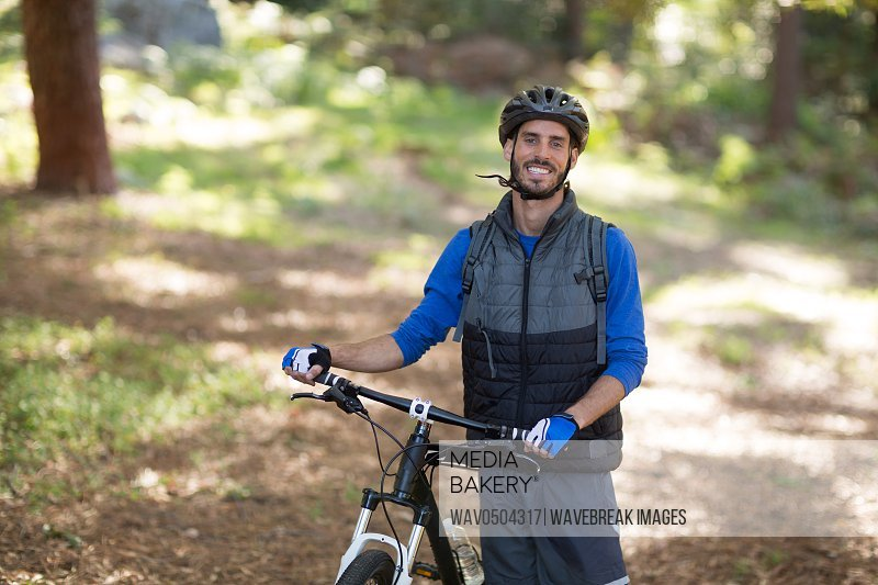 Portrait of male biker standing with mountain bike in forest
