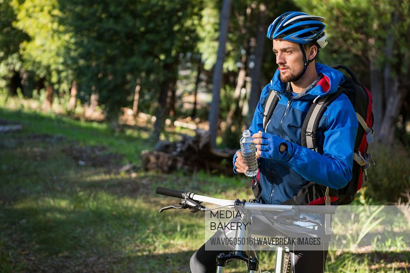 Male mountain holding water bottle standing with bicycle in the forest