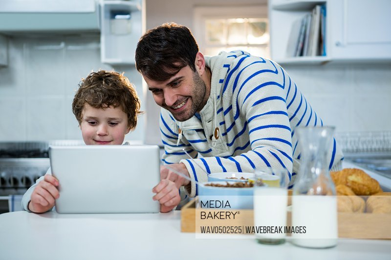Father and son using digital tablet in the kitchen at home