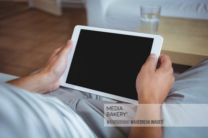 Mid section of man using digital tablet in living room at home