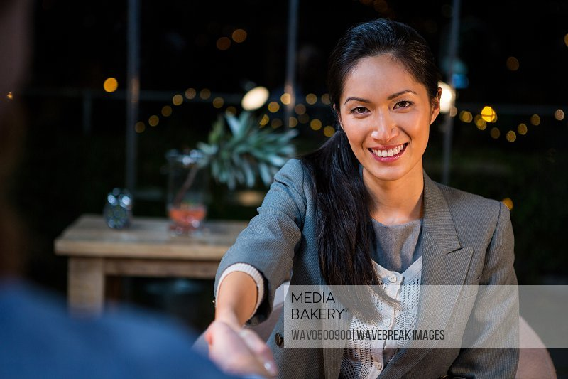Portrait of businesswoman shaking hands with colleague in the office