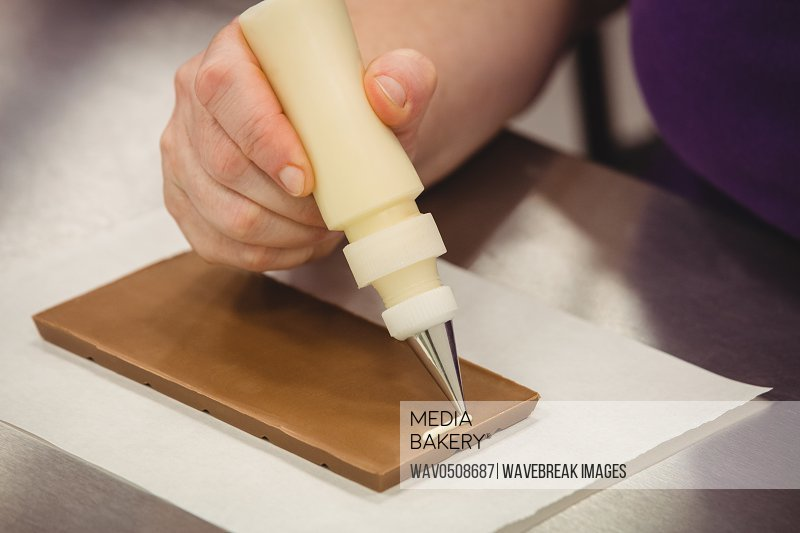 Worker writing with piping bag on chocolate plaque