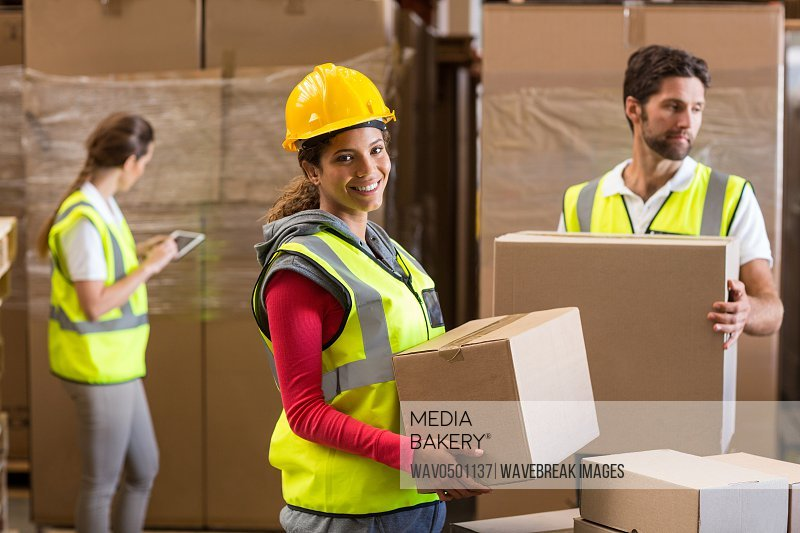 Portrait of warehouse worker carrying a cardboard box in warehouse