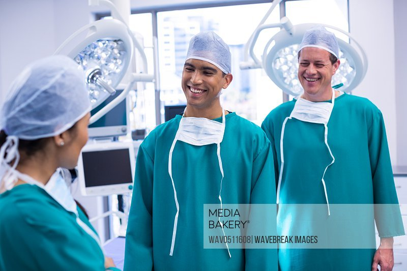 Smiling surgeons interacting with each other in operation room at hospital