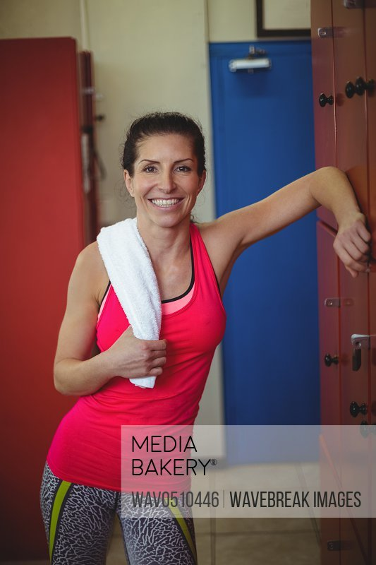 Portrait of cheerful woman standing in locker room after workout