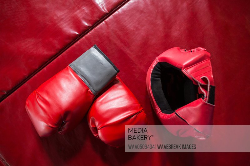 Pair of boxing gloves and headgear on red surface