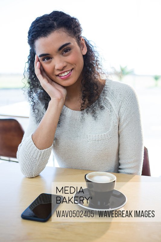 Portrait of a beautiful woman sitting with cup of coffee on table in coffee shop