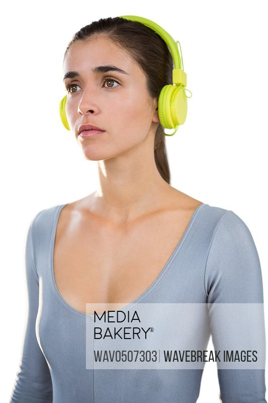 Woman in exercise outfit wearing headphones on white background