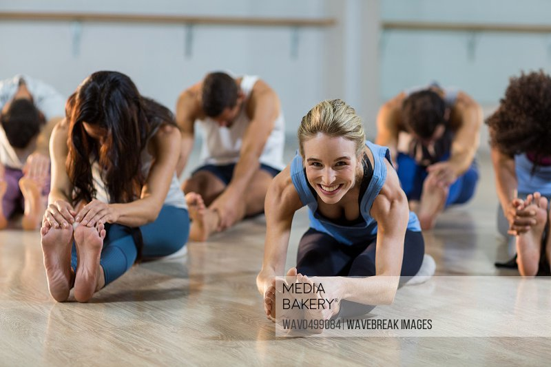 Group of people performing yoga in fitness studio